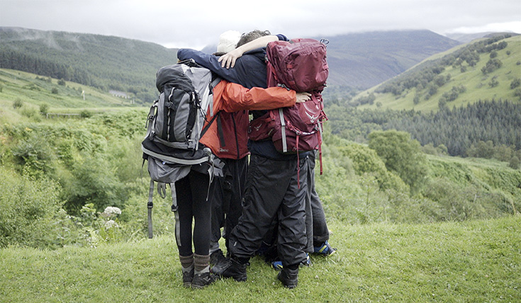 Three people, wearing hiking backpacks, hugging