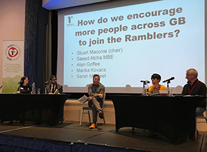 People seated behind tables, on a stage with a screen behind asking 'How do we encourage more people across GB to join the Ramblers?'