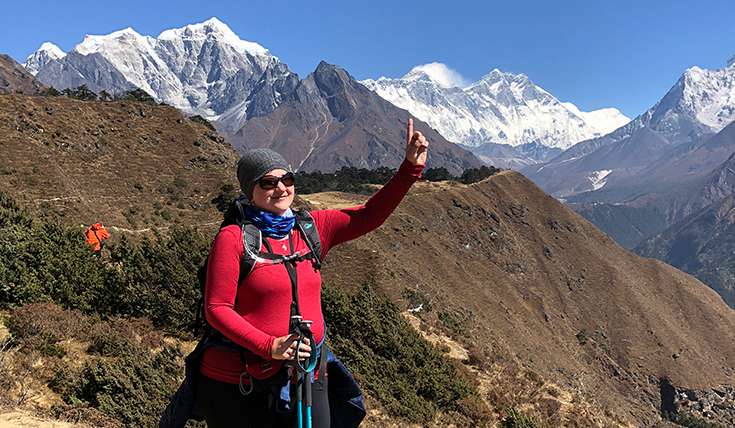 A woman standing outdoors, pointing up towards a mountain range