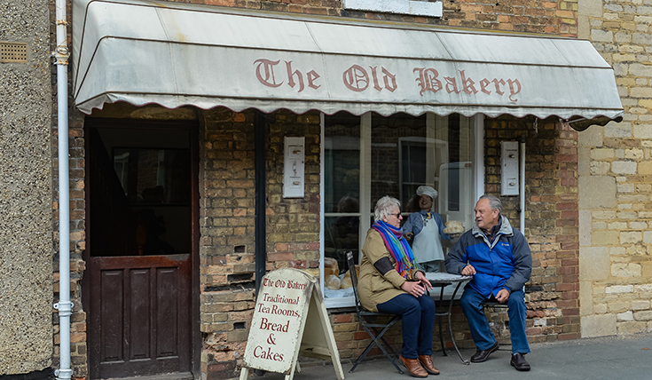 Man and women sat outside The Old Bakery Traditional Tea Rooms in the Deepings