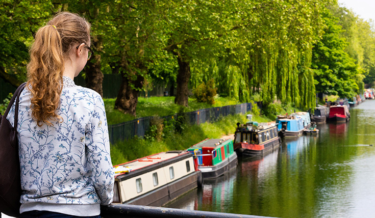 Young girl standing on bridge and looking out over canal, green trees and canal boats.