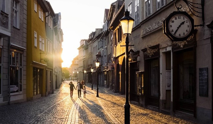 Couple with young child walking down cobbled street lined with lampposts at sunset.