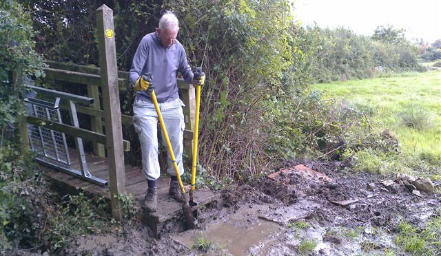 A man standing by a muddy path, using a large tool