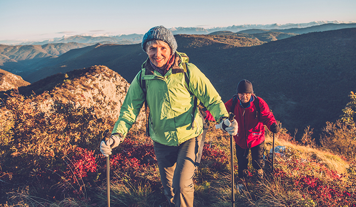 Two walkers with walking poles on a mountain.