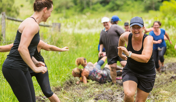 Women doing a mud run challenge event.