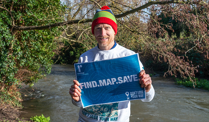 "A man, outdoors, by a stream, holding a blue sign which states ""Find. Map. Save"""