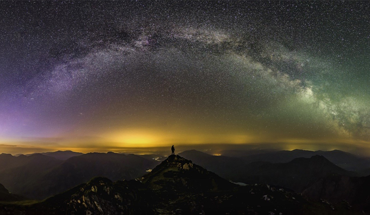 Person standing on a mountain top beneath the milky way
