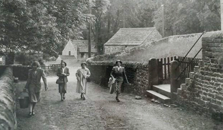 Black and white photo of four women walking in dresses and hats.