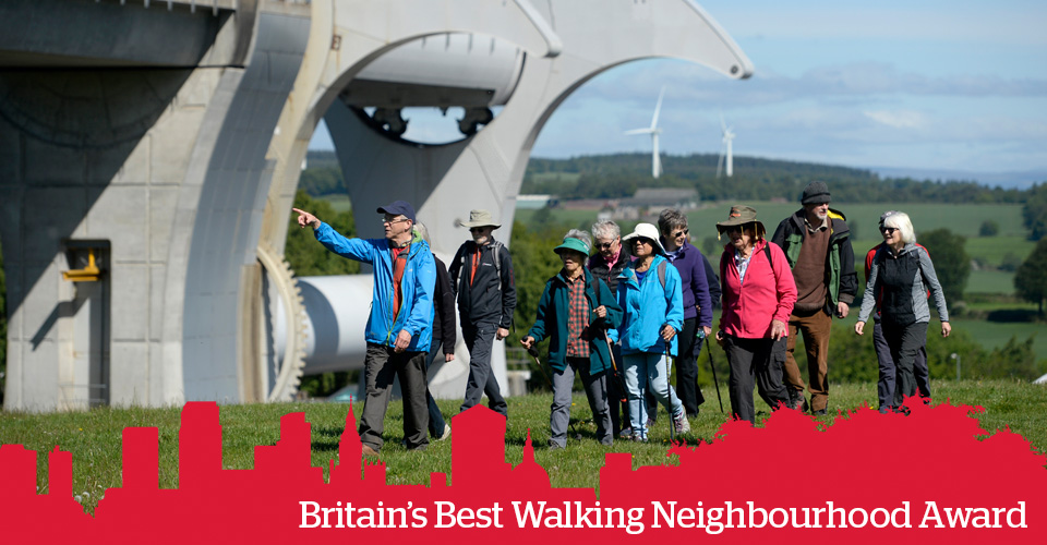 A group of people walking together outdoors, by a steel sculpture. Text: Britain's Best Walking Neighbourhood