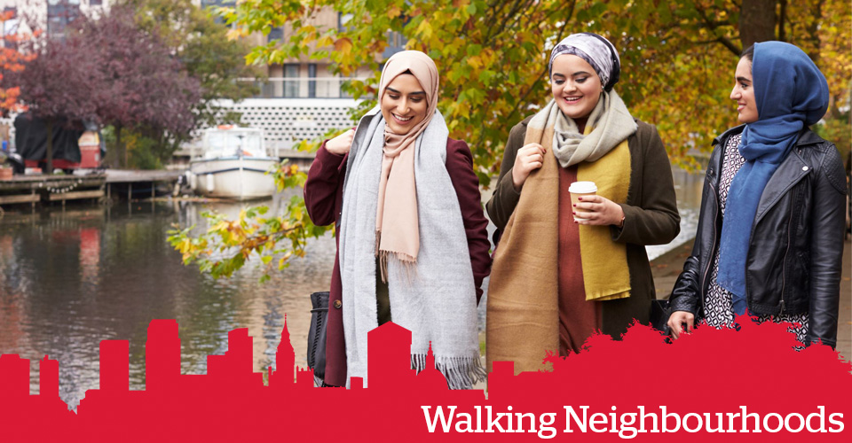 Three women in head scarves, walking beside a canal. Text: Walking Neighbourhoods