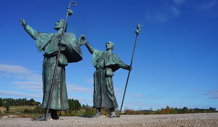 Two statues of men, holding poles and reaching in to the air
