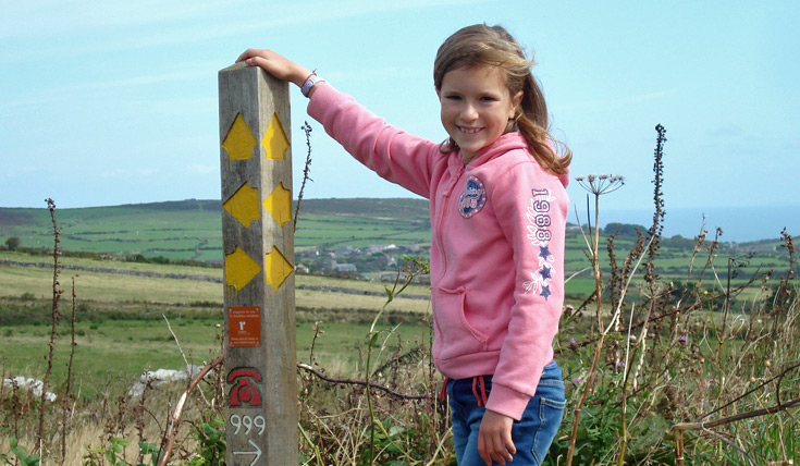 Girl stands at path sign