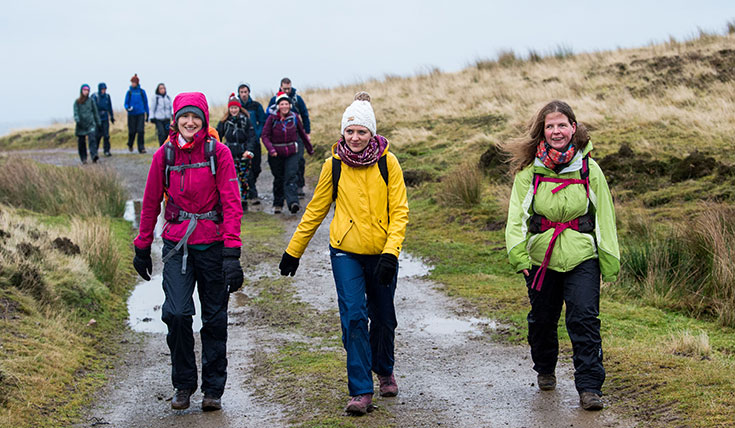 Three young women, dressed warmly, walking along a wet path, high in the hills