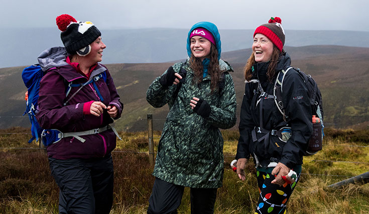 Three young women, dressed warmly, laughing