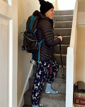 A young woman, dressed in mountain hiking gear, walking up the stairs