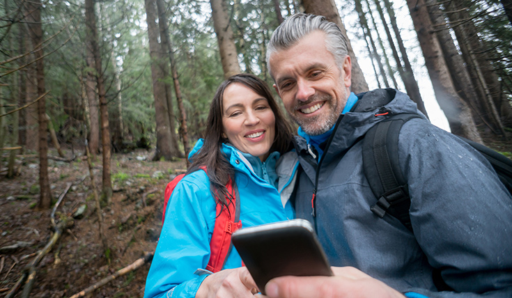 A couple, in the woods, looking at a mobile phone