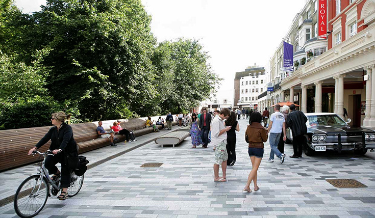 A paved urban street with cyclists, pedestrians and shops