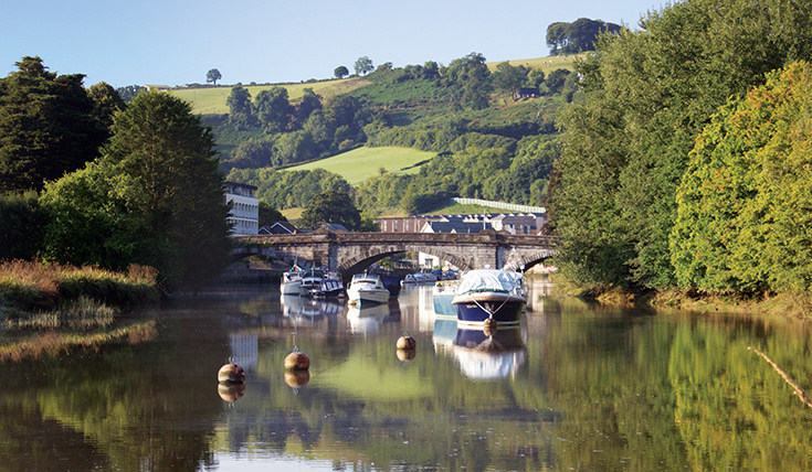 Boats on the river Dart in the early morning, trees and hills.