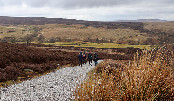 People walking on path in the Yorkshire Dales in Autumn, rolling hills.