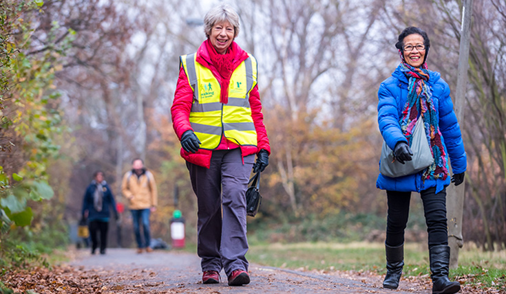 Two women walking in Autumn, one wearing a Walking for Health Jacket.