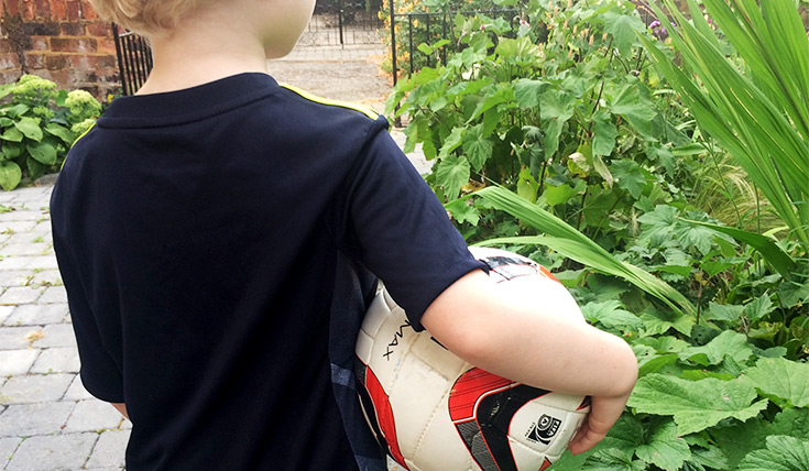 A young boy holds a football whilst walking in a garden path