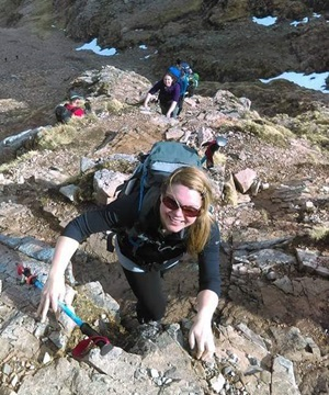 A woman scrambling up a rocky slope