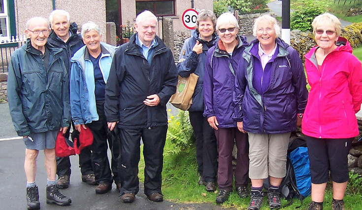 A group of older people outdoors, in a town