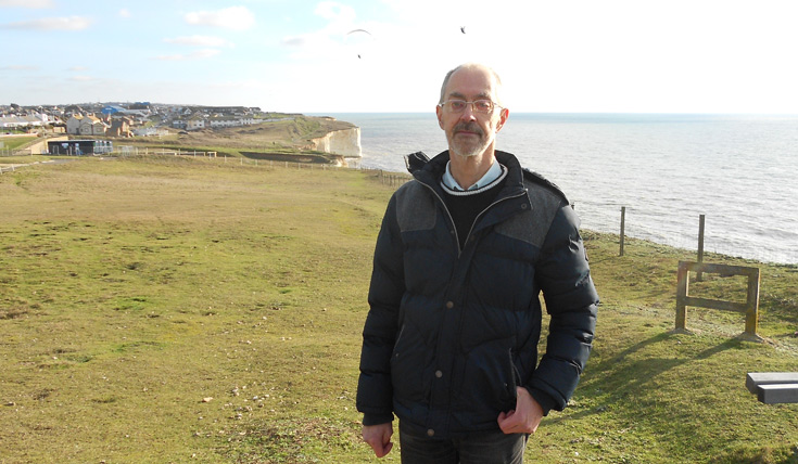 A man standing outdoors, in front of white cliffs