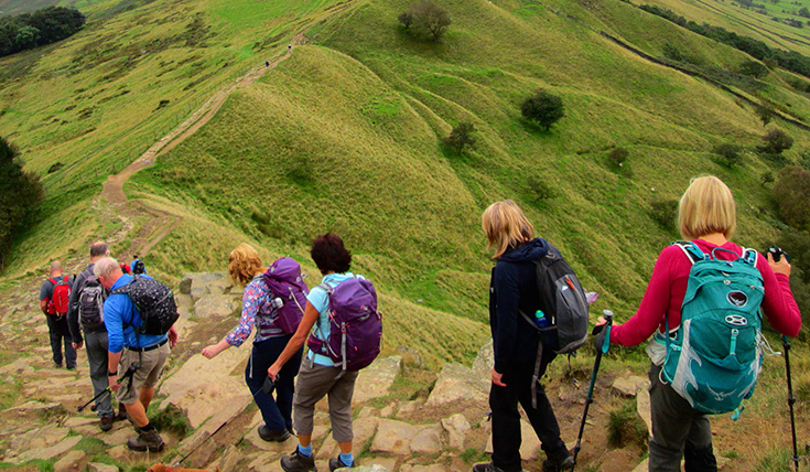 A group of walkers descending a steep grassy hill
