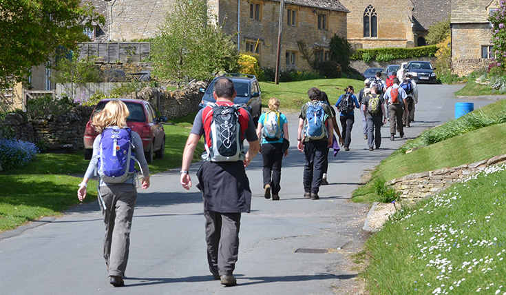 A group of walkers heading along a village road