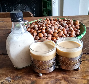 Bowl of hazelnuts and two glasses, full of milk
