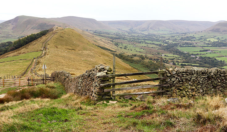 A view down a valley with hills, stone walls and a wooden gate