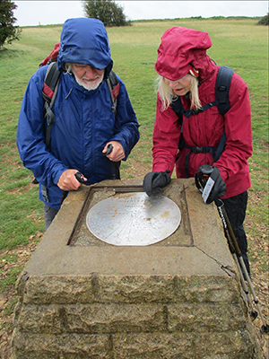 Two people examining a stone trig marker