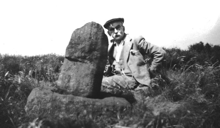 Black and white photo of a man sitting beside a rock