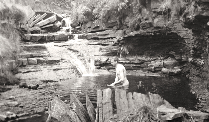 Black and white photo of man skinny dipping in a rock pool