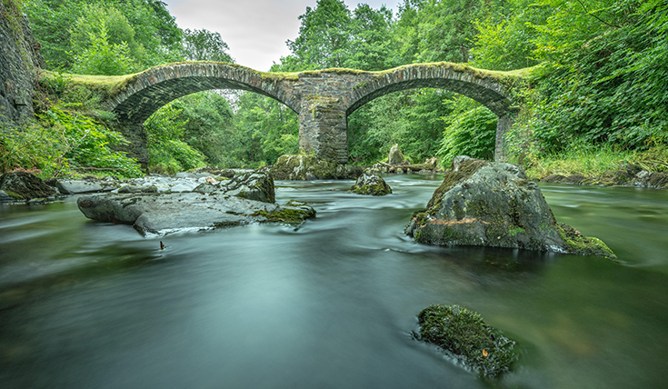 stone bridge with two arches, over a river