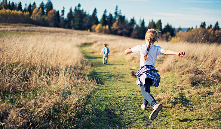 Two young children running down a grassy path
