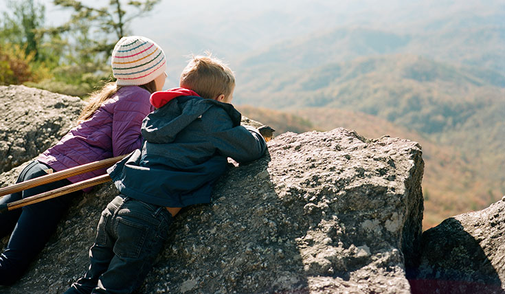 Two children looking out at a view, over a rock