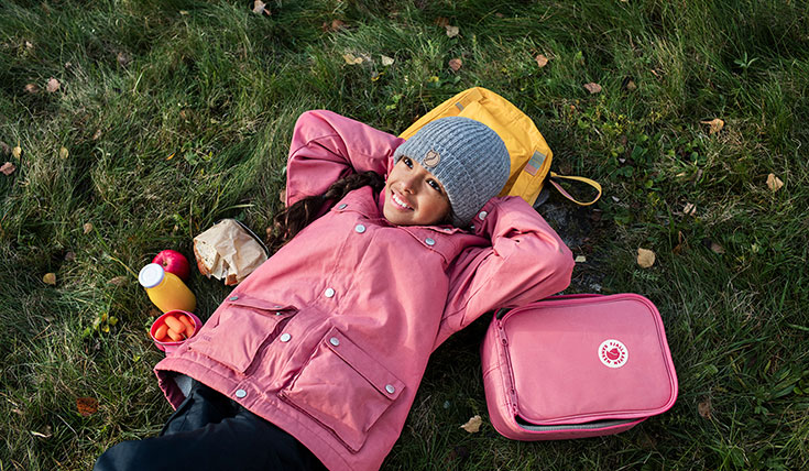 A girl lying on the ground with a backpack and flask