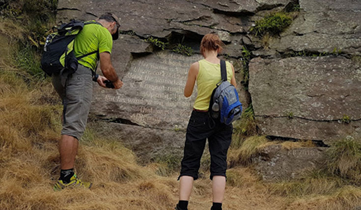 Two people looking at inscriptions on a stone