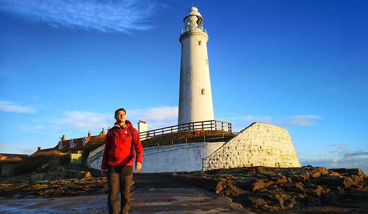 A man in front of a lighthouse