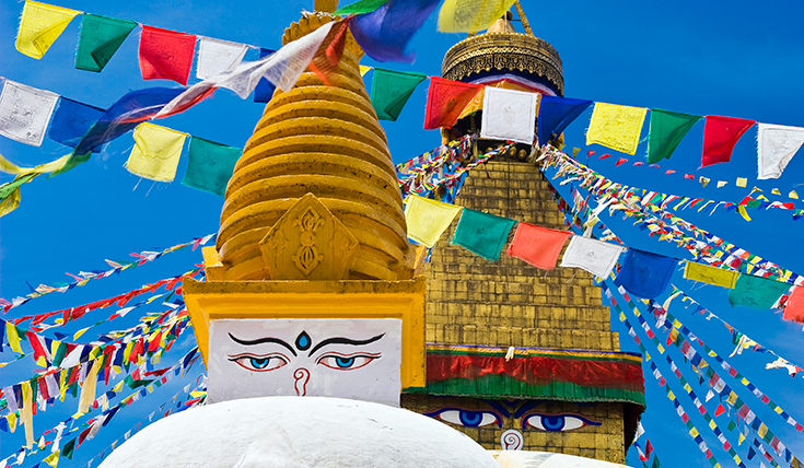 Prayer flags surrounding a buddha statue