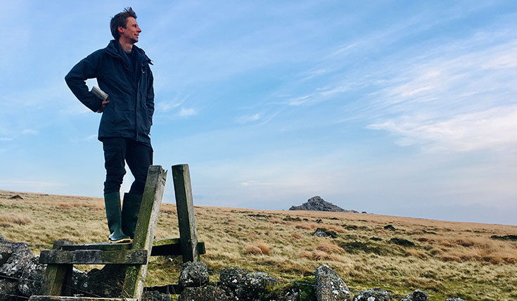 A man standing on a stile, looking over a vista
