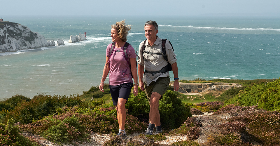 A woman and man walking a path by the coast
