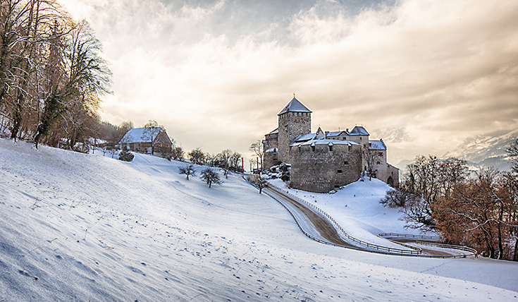 A snow covered landscape with a castle and winding road