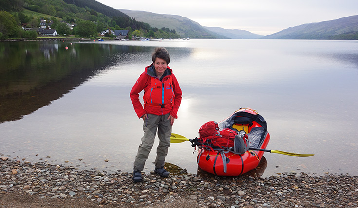 A woman standing on a lake shore, beside a kayak