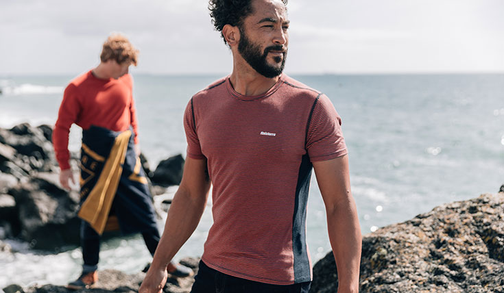 A man standing by the coast, wearing a T shirt