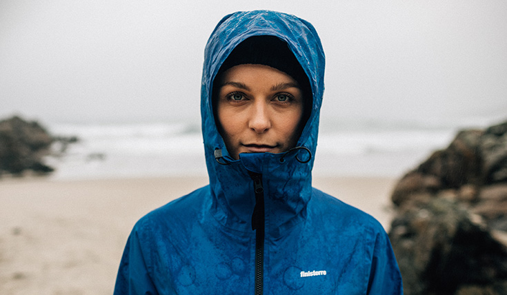 A woman outdoors, wearing a blue waterproof jacket, with the hood up