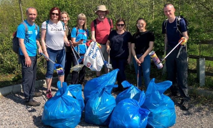 Group of people standing on a path in the countryside in front of several bags full of rubbish. They are all holding litter picking sticks.