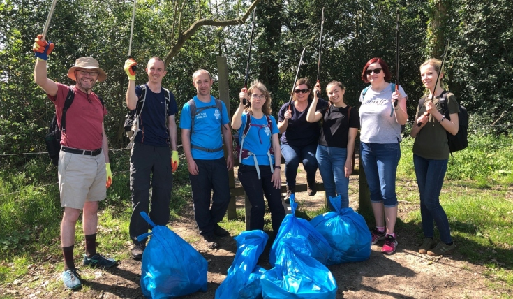 Group of people on country path with bags full of rubbish, holding litter picking sticks aloft